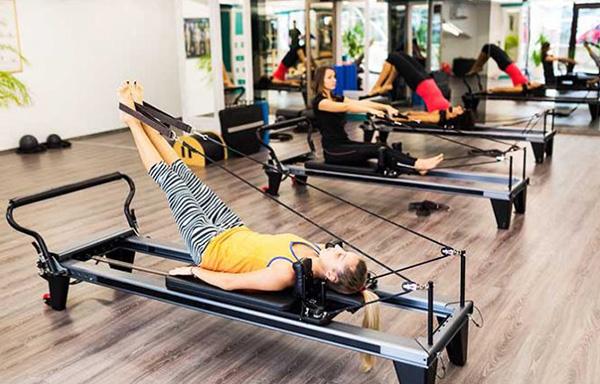 Trois jeune femmes réalisant des exercices de cardio pilates avec des machines de sport adaptées
