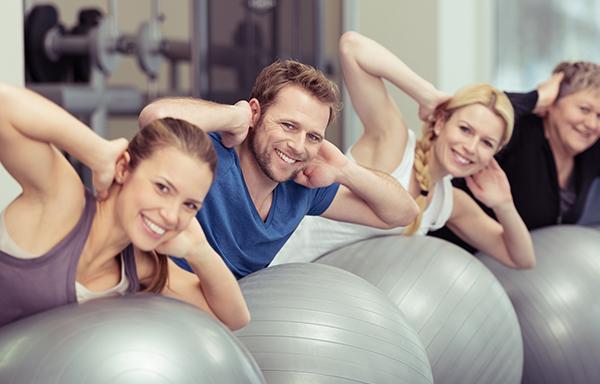 Groupe de personne souriante participant au cours de Global Gym